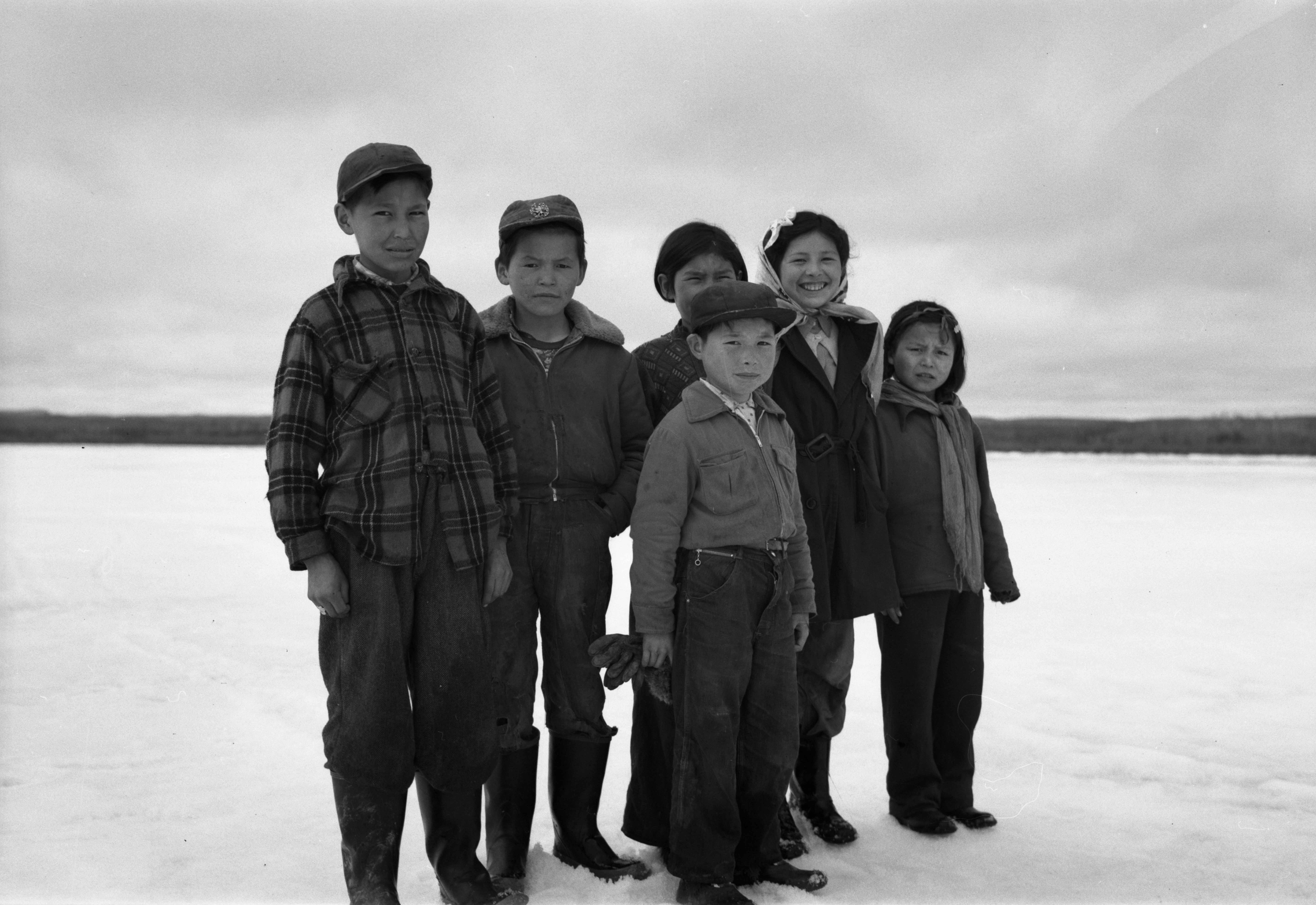 Five First Nations children standing on the ice/snow.
