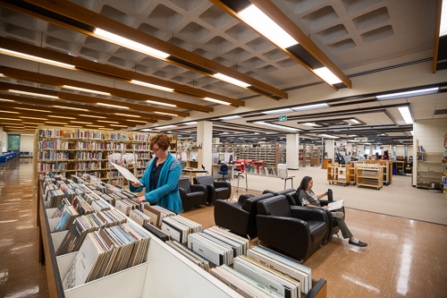 A person looking at records and a second seated person reading and drinking coffee inside the Education and Music Library.